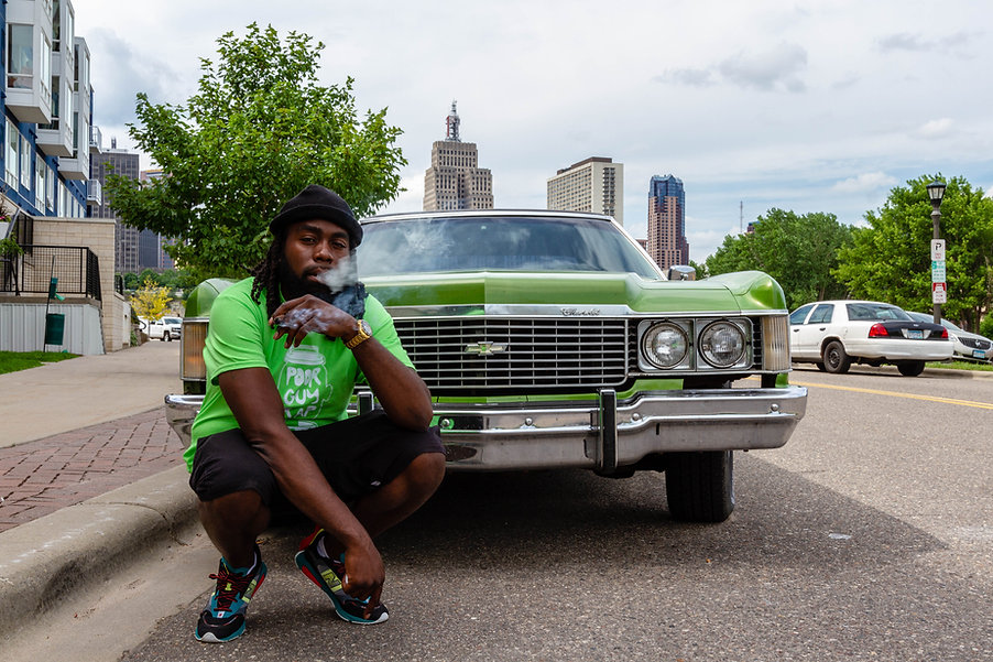 Rob-1 smoking a blunt by a Cadillac Poorguyrap limited lime color shirt
