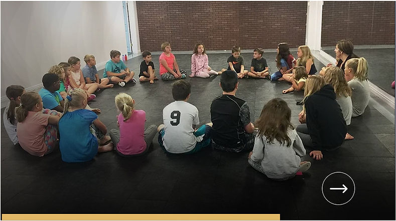 group of students sittiing in a circle formation