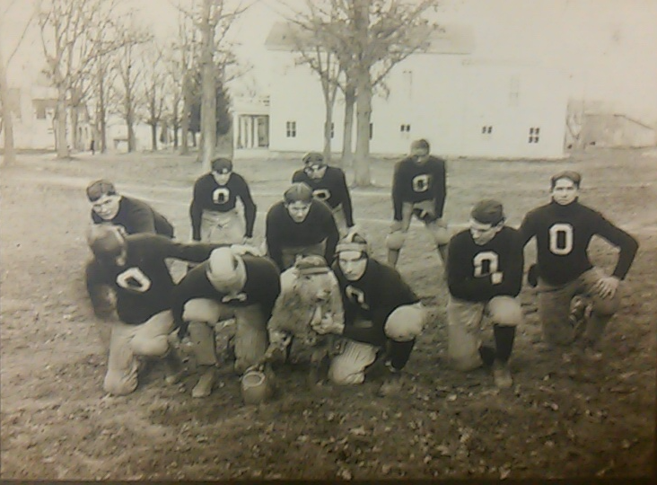 1900-1902 the football team takes a photo break with their unofficial sheep mascot.