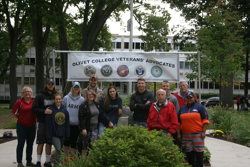 Students pose in front of the plaque during service day