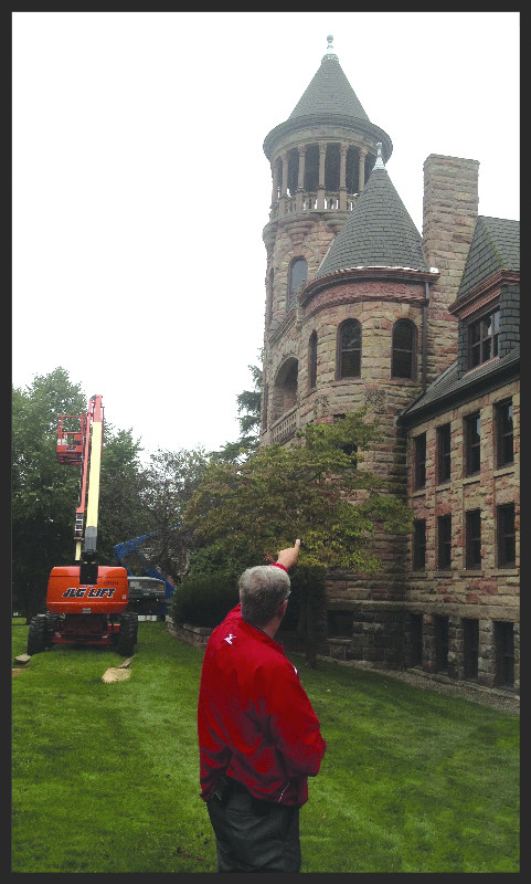 Frank Schumacher points to one of the brick turrets on the Burrage Library to a group of students during a campus tour.