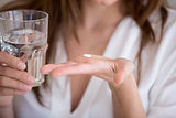 Woman holding pill and glass of water in