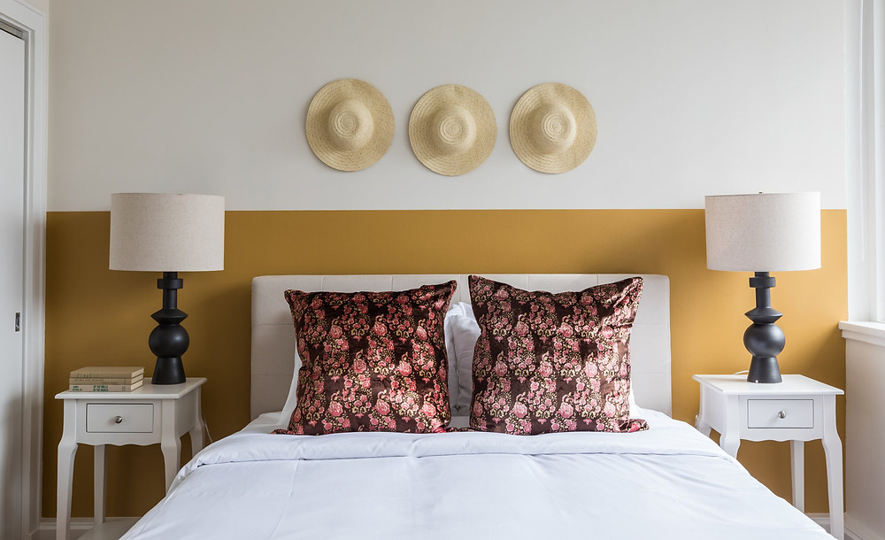 Bedroom designed by Sun Soul Style Interiors. Hats on wall yellow marigold paint accent wall