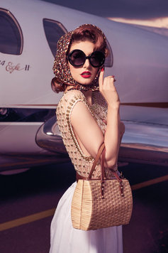 glamorous 50s woman in sunglasses standing next to a plane