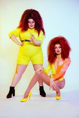 two drag queens in neon costumes