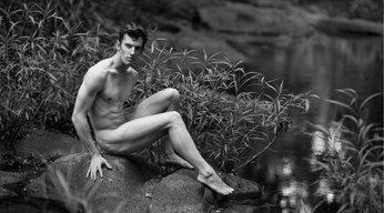 black & white nude man next to a creek