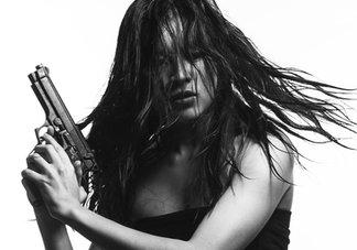 asian woman holding gun in black & white