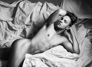 black and white man lying in bed sheets