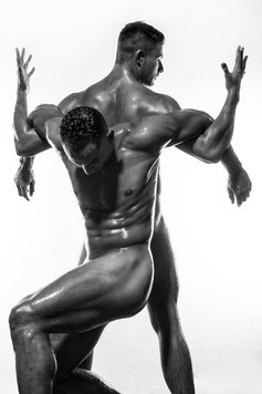 two oiled athletes in black and white