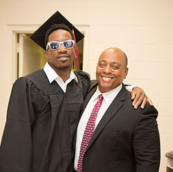 A Kingsman Academy student and staff member smile at graduation.