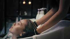 Hairdresser softly wraps woman's long bl