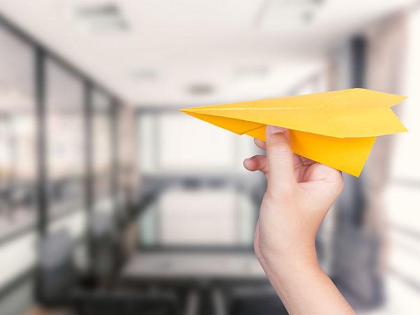 hand holding paper plane on office backg