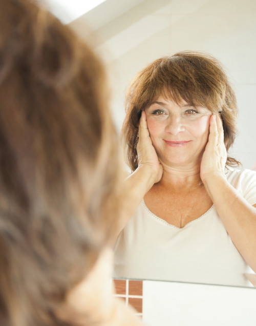 Woman in mirror with dry, dehydrated skin