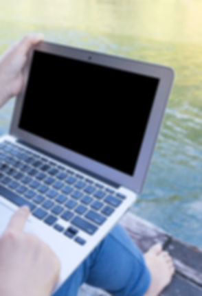 Young woman sitting on pier using laptop