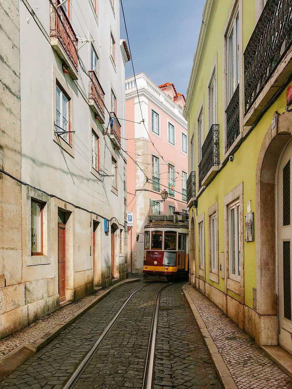 lisbon tram coming through narrow streets cobblestone streets