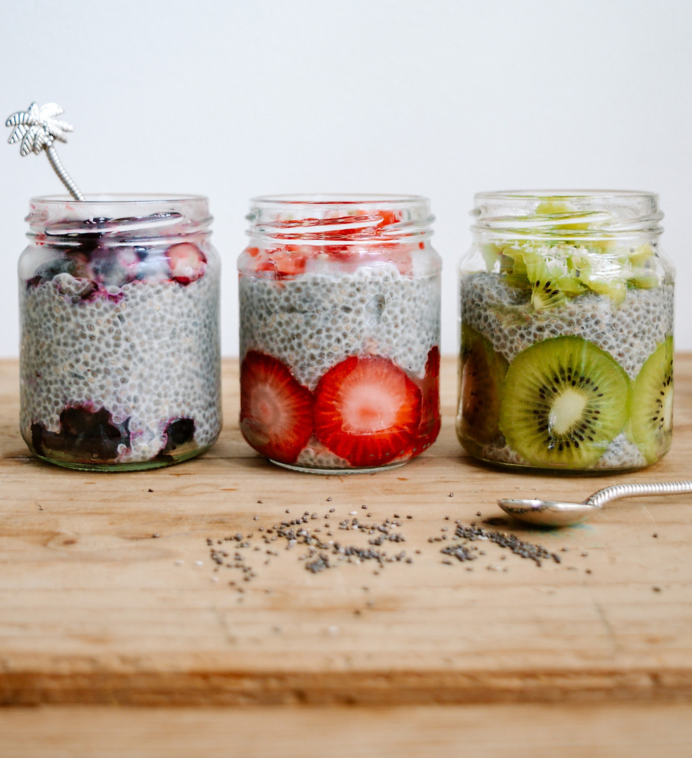 chia seed pudding with blueberries, strawberries and kiwi fruit in three glass jars