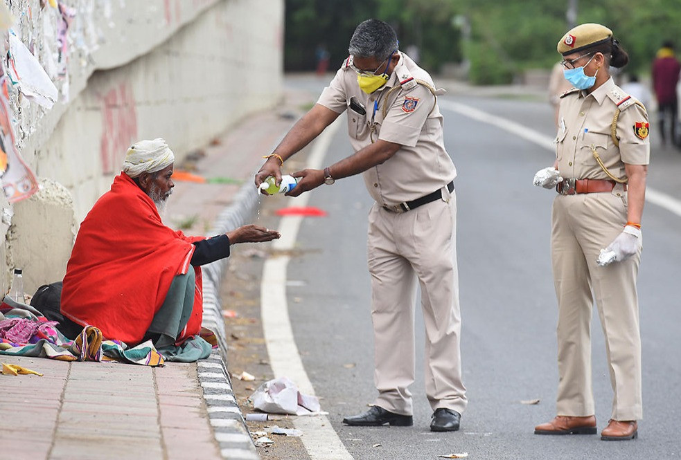 A street beggar in Delhi in India is given hand sanitizer by two armed policemen
