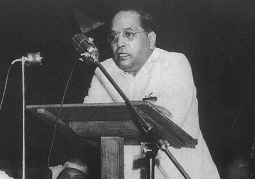 R B Ambedkar delivers an address from a lectern to a large group of supporters in India in 1947