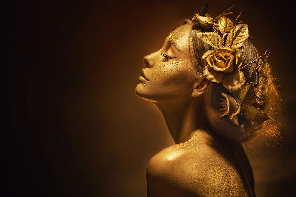 Portrait Closeup Beauty fantasy woman, face in gold paint. Golden shiny skin. Fashion mode