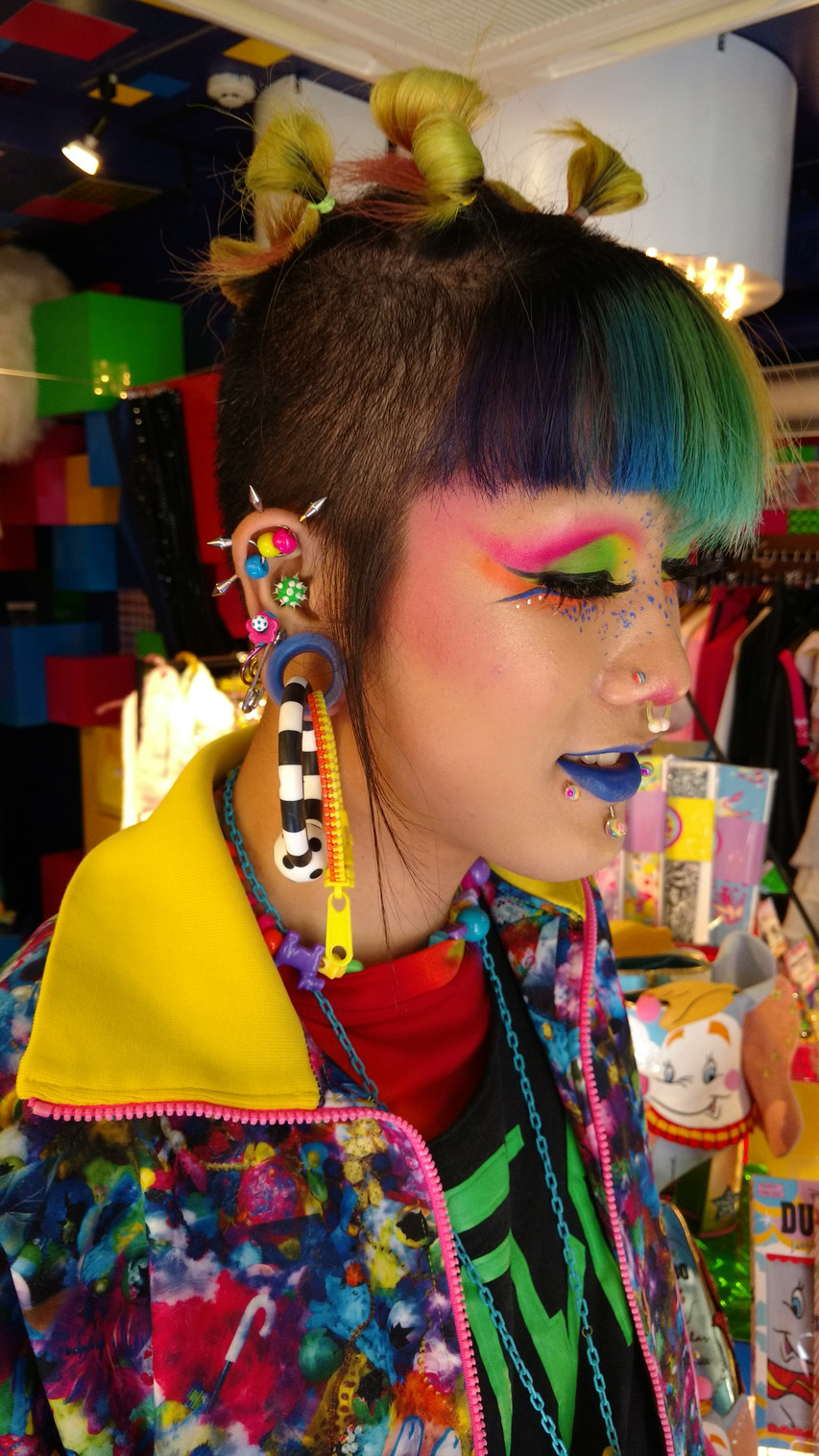 His colourful hair and fun make up match perfectly with all his earrings!