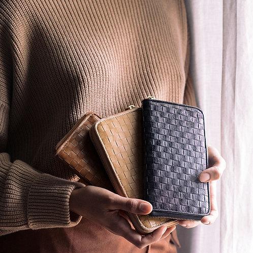drei geflochtene Geldbeutel in der Hand einer Frau