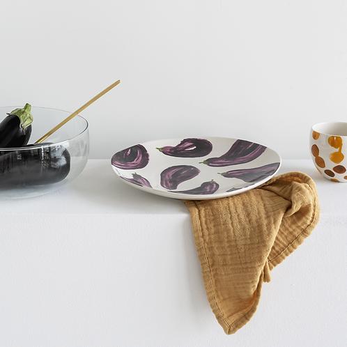 weisser Teller mit lila Auberginen und gelbem Handtuch