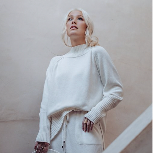 blonde Frau trägt wollweißen Pullover