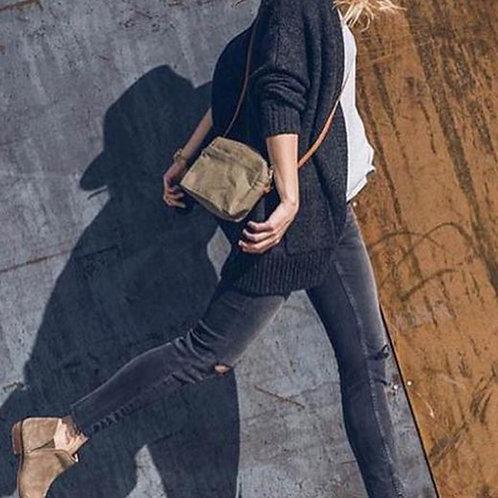 gehende Frau mit olivefarbener Handtasche Tracolla von Uashmama dazu trägt Sie eine schawarze Jeans und hellbraune Boots