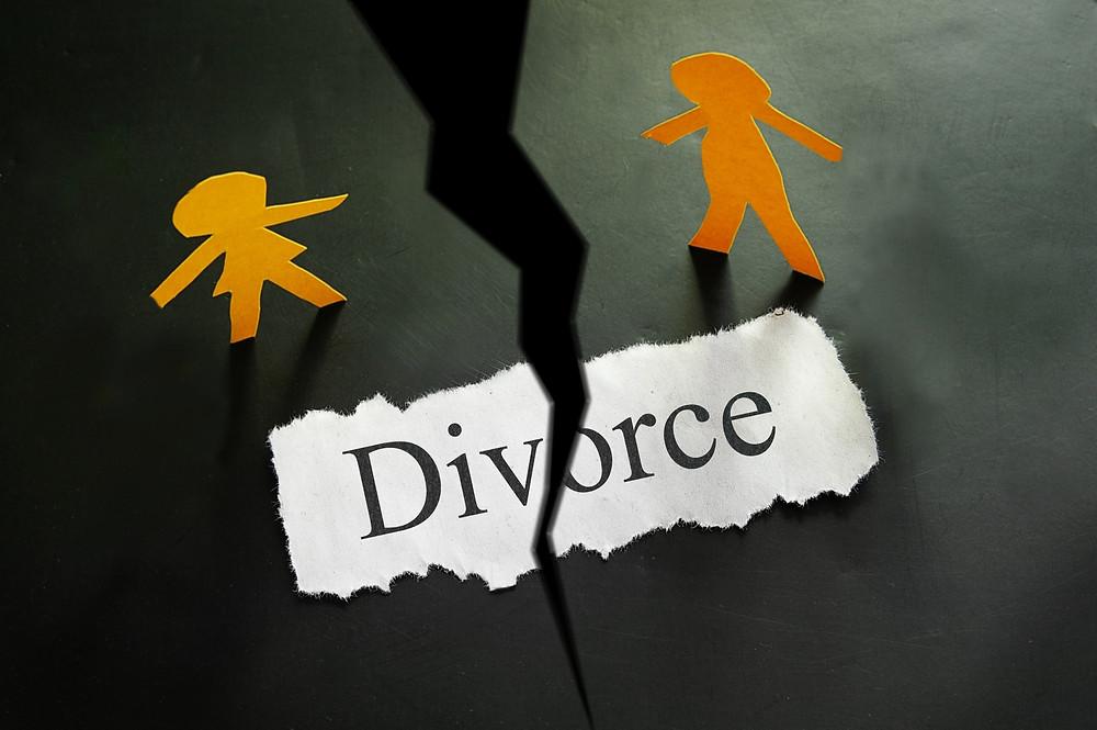 שתי דמויות אנושיות מגזירות נייר כתום וצהוב ופתק שכתוב עליו divorce באמצע קרוע ביניהם