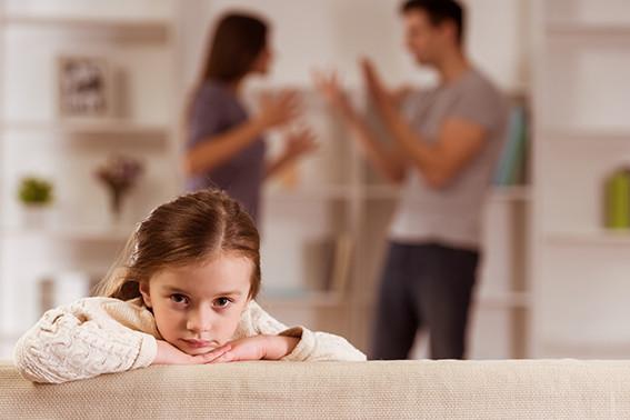 ילדה קטנה נשענת על הידיים שלה עם פרצוף עצוב וברקע ההורים שלה מתווכחים