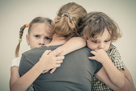 אמא עם הגב למצלמה מחבקת את שני הילדים הקטנים שלה שניהם עם הפנים למצלמה ושניהם נראים עצובים