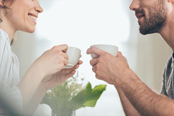 גבר ואשה יושבים אחד מול השניה ומחזיקים כוס קפה, מחייכים אחד לשנייה