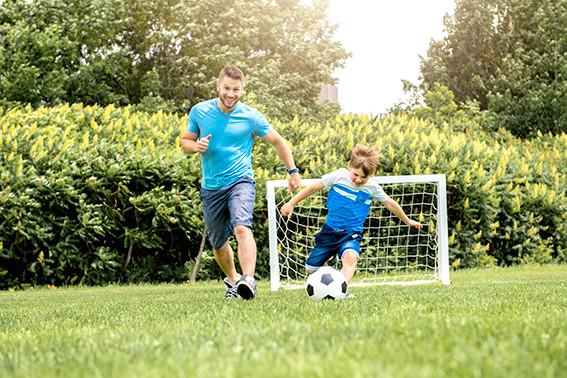 אבא ובן לבושים בבגדים כחולים משחקים כדורגל על הדשא הירוק
