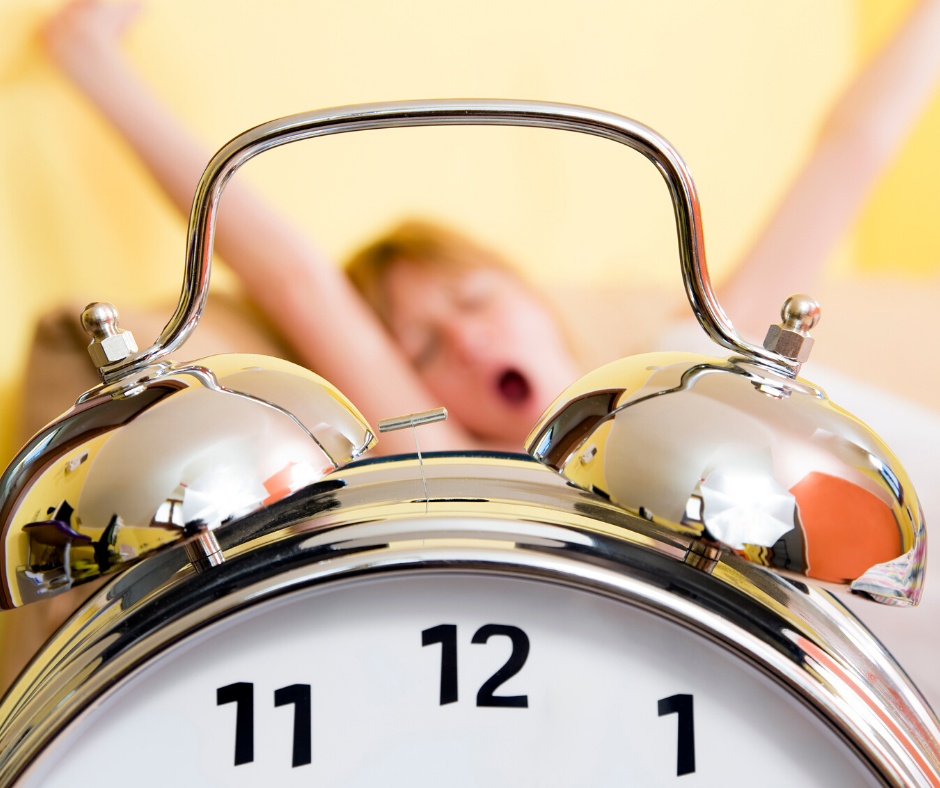שעון מעורר ואשה שוכבת במיטה, מפהקת ומתמתחת ברקע
