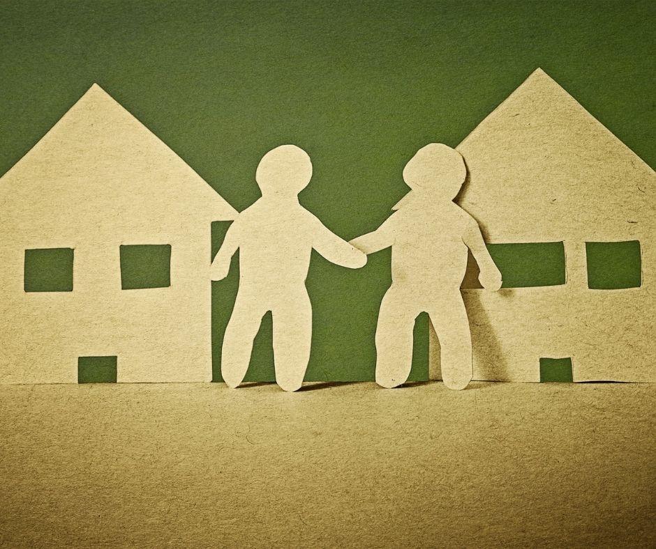 שני בתים מגזירות קרטון ושתי דמויות אנושיות מגזירות קרטון אוחזות ידיים