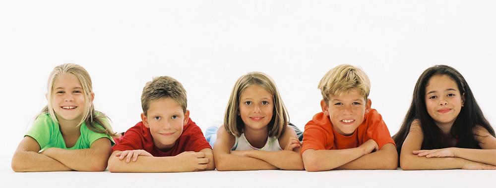 שישה ילדים בשורה שוכבים על הבטן, משלבים ידיים ומחייכים עם הפנים לכיוון המצלמה