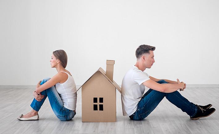 גבר ואשה לבושים בג'ינס כחול וחולצה לבנה יושבים על הרצפה ונשענים גב אל גב על בית מקרטון שנמצא ביניהם
