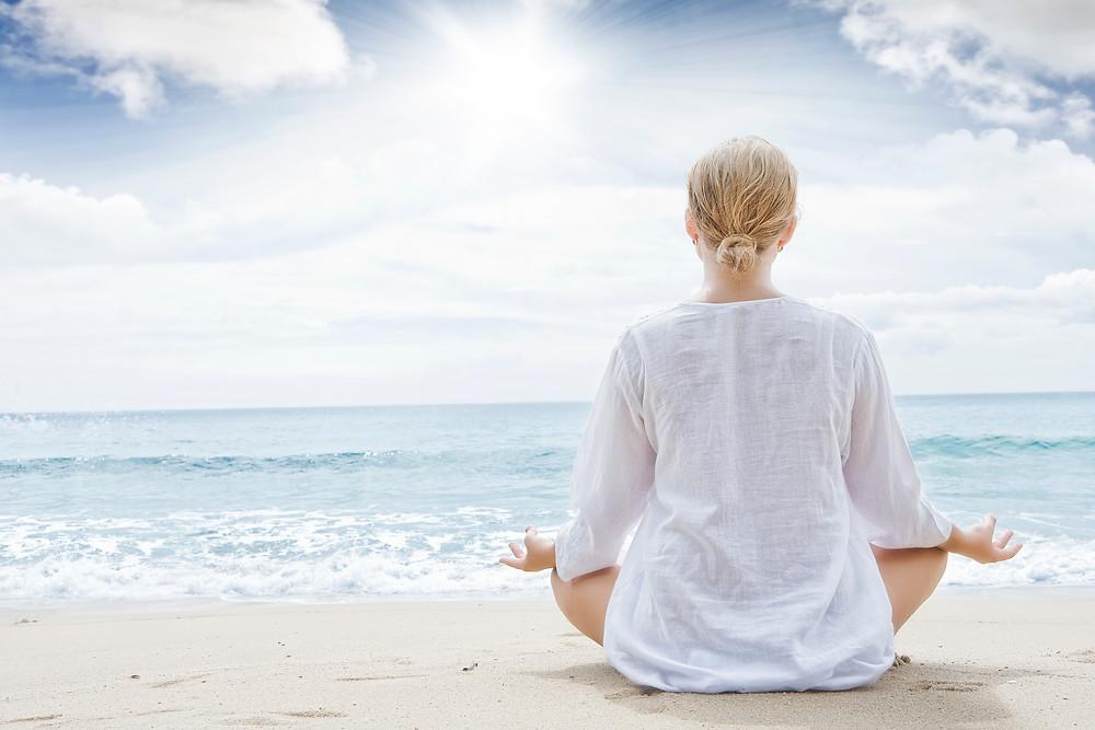 אשה יושבת על החול בחוף הים לבושה בלבן ועושה מדיטציה עם הגב למצלמה