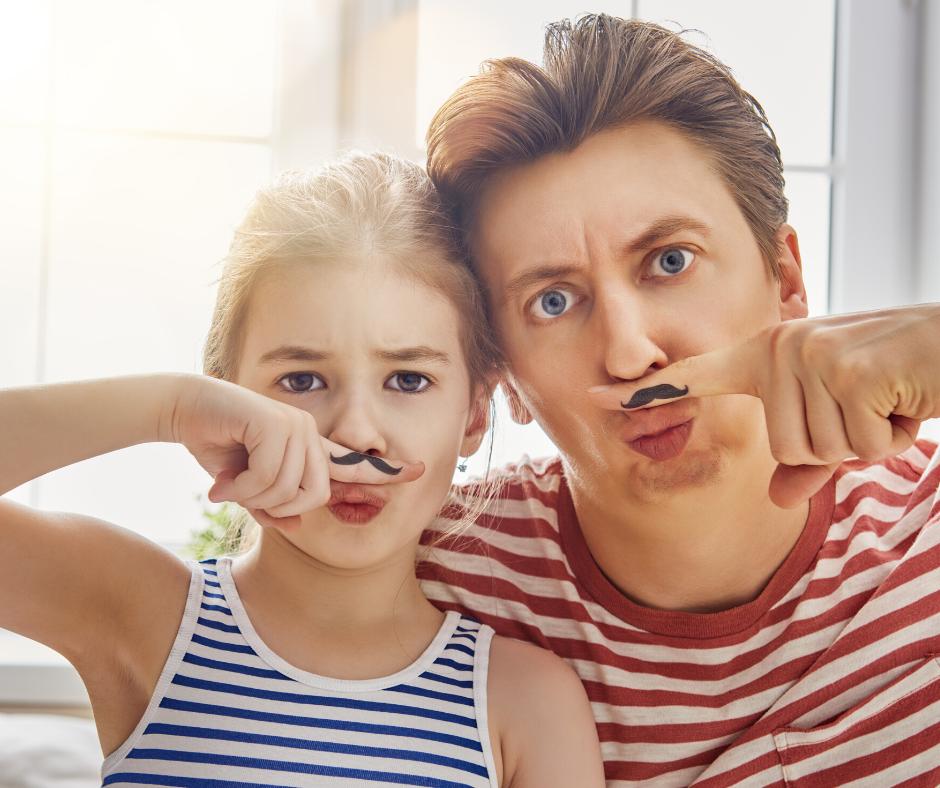 אבא וילדה קטנה שנראים דומים, שניהם לובשים חולצת פסים. לשניהם יש ציור של שפם קטן על הצד של האצבע ושניהם שמים את האצבע בין האף לפה כאילו שהשפם ממוקם שם.