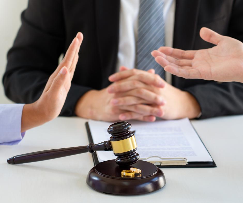 עורך דין או מגשר עם חליפה ועניבה, אצבעות ידיים משולבות נשענות על שולחן. על השולחן פטיש של שופטים ושתי טבעות נישואין על גבי מסמך מנייר. בשני צידי התמונה כפות ידיים אחת מול השניה בתנוחה של ויכוח