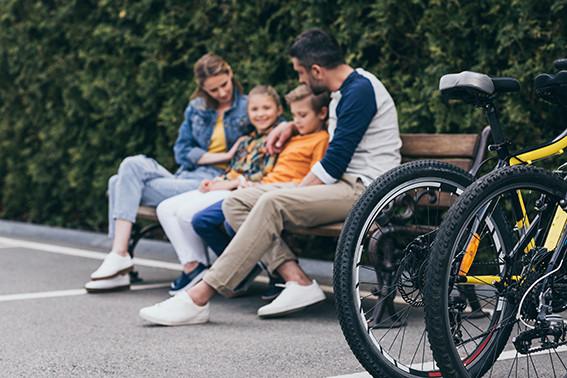 אמא ואבא ובניהם ילד וילדה יושבים על ספסל ברחוב ומדברים ובצד שני זוגות אופניים