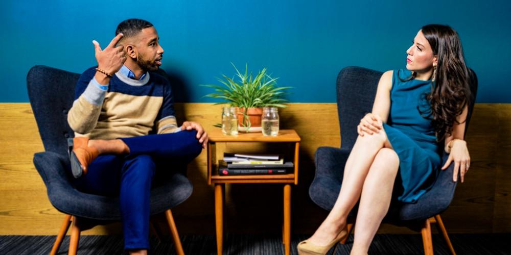 Arabisch aussehender Mann und mitteleuropäisch aussehende Frau, beidezwischen 30 und 40, Business Casual gekleidet, sitzen auf Sesselln, ein Tischchen zwischen sich und diskutieren mit ernsten Gesichtern