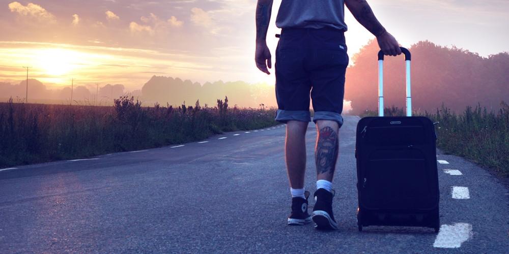 Junger Mann in T-Shirt, kurzer Hose und Turnschuhen geht im Sonnenuntergang mit einem Koffer am Rand einer Landstraße