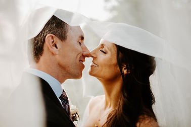 happy bride and groom kissing under veil