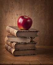 Stack of books and red apple on wooden t