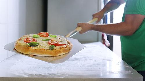 פיצה קאסה דל פפה רחובות פיצה כשרה במשלוח עד הבית . בתמונה פיצה בלקאנית מונחת על קרש עץ באלכסון