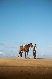 A girl stood on the beach holding a horse.
