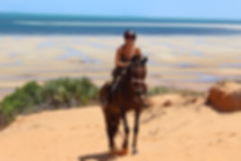 A woman on a horse, riding on a sand dune in Mozambique.
