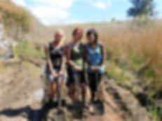 Three girls with shovels covered in mud.