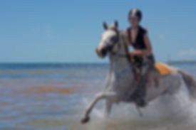 A girl galloping a grey horse through the sea in Mozambique.